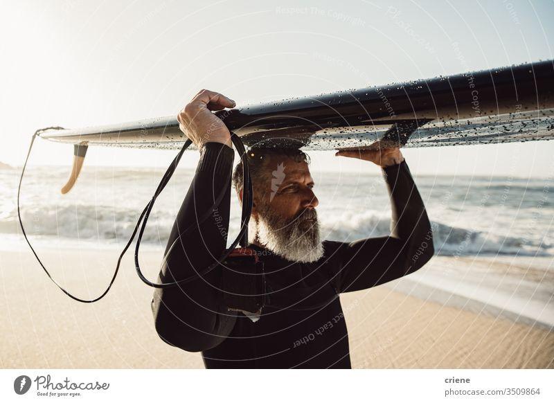 Kaukasischer älterer Mann mit Bart, der ein Surfbrett auf dem Kopf trägt Senior Männer Urlaub Strand Surfen Erwachsener graue Haare Lifestyle Sport Hobby