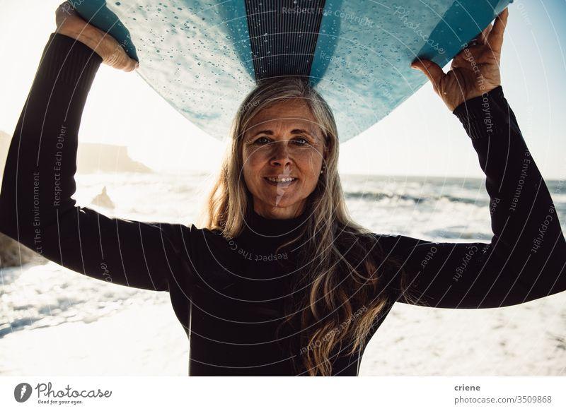 Lächelnde ältere Frau trägt Surfbrett am Strand und schaut in die Kamera Senior Frauen Urlaub Surfen Erwachsener graue Haare Lifestyle Freude Kaukasier Sport