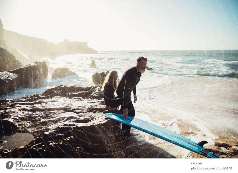 Älteres Ehepaar sitzt zusammen auf Felsen mit Surfbrettern und macht eine Pause Paar Zusammensein Senior Männer Urlaub Strand Surfen Erwachsener Vollbart