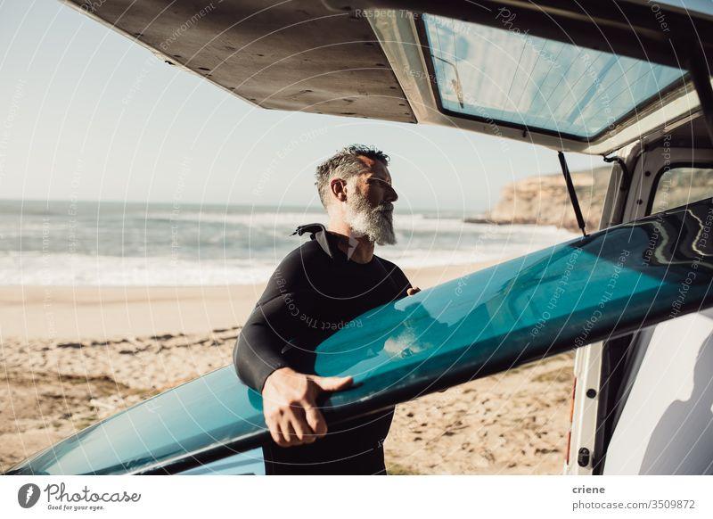 Älterer Mann nimmt am Strand Surfbrett aus Lieferwagen Senior Männer Kleintransporter Verkehr Ausflug Urlaub Surfen Erwachsener Vollbart graue Haare Lifestyle