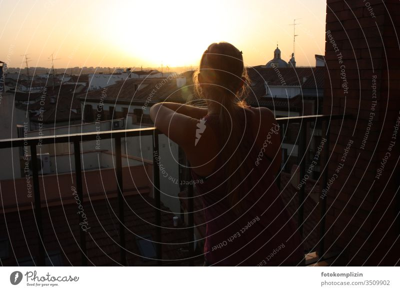 junge Frau blickt bei Abendsonne über Stadt Dächer dächer Balkon Großstadt Stadtbild nachdenklich melancholie betrachtend Gegenlicht urban Weitblick Skyline