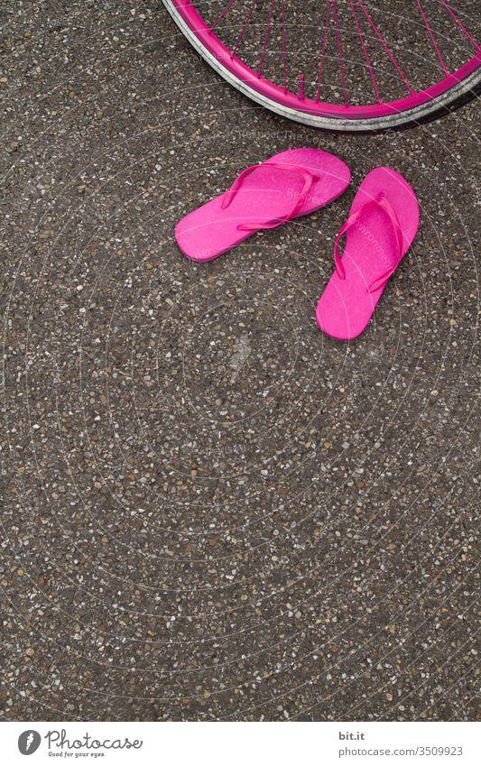 Knallig pinke Flip Flops, stehen herrenlos im Sommer auf dem Asphalt der Straße, vor einem Fahrradreifen in Pink und warten auf ihren Besitzer. Flipflops Rad