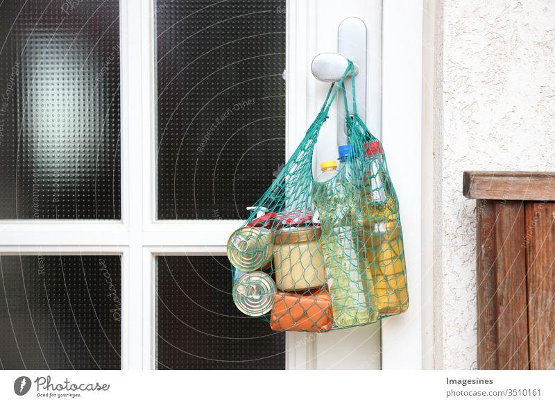 Lieferung von Lebensmitteln im Einkaufsnetz während der Coronavirus Infektion Covid-19 Quarantäne. Einkaufstasche, Netzbeutel mit Einkauf, Waren, Essen hängt an der Haustür, Nachbarschaftshilfe. Hilfe von schutzbedürftigen Menschen Konzept