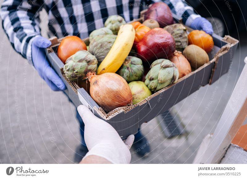 Kaukasischer Freiwilliger Mann übergibt die Schachtel aus dem Lebensmittelladen an eine Frau zu Hause.beide mit medizinischen Handschuhen.Freiwilliger und Lieferkonzept