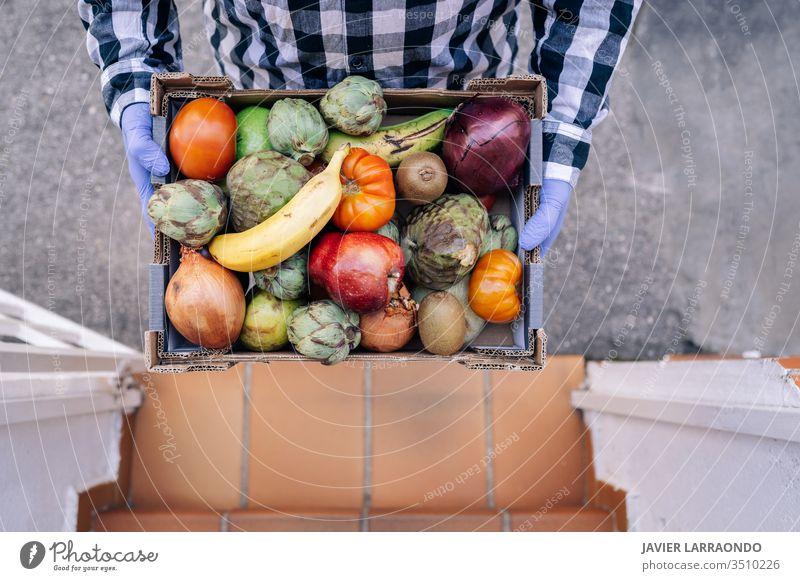 Männlicher Freiwilliger, der eine Kiste mit Gemüse und Obst in einer Haustreppe hält. Freiwilliger Helfer, Abriegelung, Epidemiekonzept Unterstützung