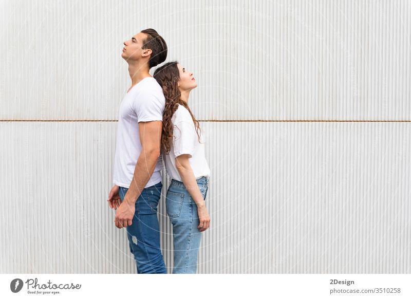 Junges Paar steht Rücken an Rücken gegen die weiße Stadtmauer Frau Mann jung Menschen männlich Mädchen Glück 2 Porträt Hintergrund Stehen schön Freizeitkleidung