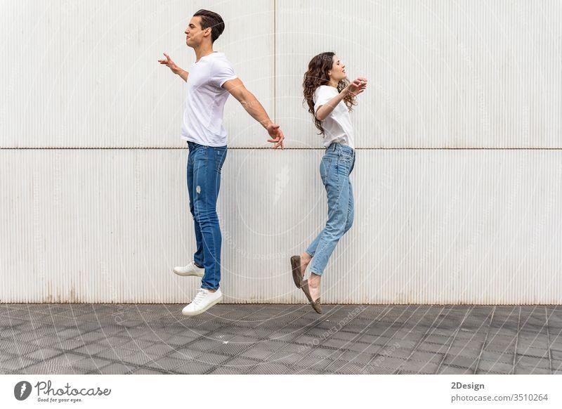 Junges Paar springt Rücken an Rücken gegen weiße Stadtmauer urban Lifestyle jung Kaukasier Frau Mann Glück Großstadt Fröhlichkeit schön Mädchen springend Spaß