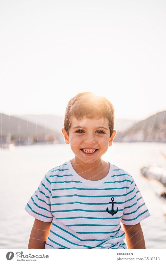 Süßes Kind lächelt bei Sonnenuntergang mit dem Meer im Hintergrund Strand schön blau Junge hell heiter Kindheit Kinder Küste Küstenlinie Farbe niedlich Gesicht