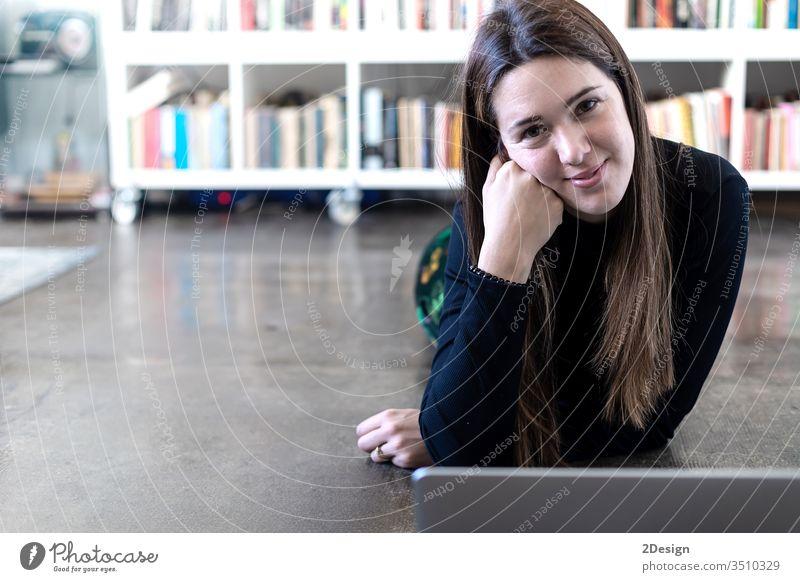 Junge, hübsche Unternehmerin, die einen Laptop benutzt, während sie zu Hause auf dem Boden sitzt. jung Frau 1 Computer Stock heimwärts Menschen Person