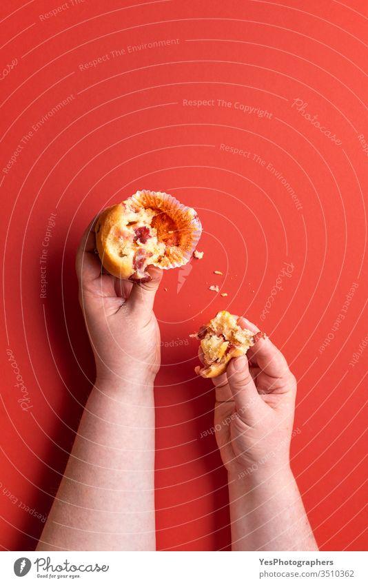 Ein Erdbeer-Muffin essen. Frauenhände, die einen Muffin halten. Frucht-Dessert 1 Schnell-Brot-Muffins obere Ansicht Amerikaner Bäckerei gebissen Frühstück