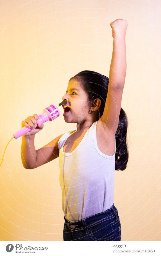 Kleines Mädchen mit Schnurrbart singt mit ihrem Mikrofon Karneval blitzen Einstellung feiern zu feiern Kinder bequem Konzepte cool Tracht Deckung Kreativität