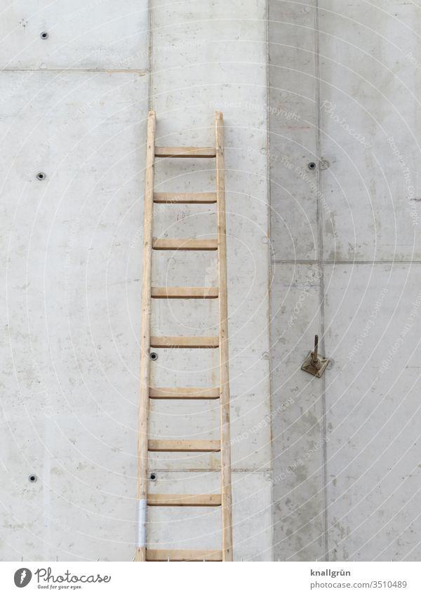 Auf einer Baustelle lehnt eine Holzleiter an einer Betonwand Leiter Sprossenleiter Wand bauen Arbeitsstelle Tag Handwerk Renovieren Außenaufnahme Farbfoto