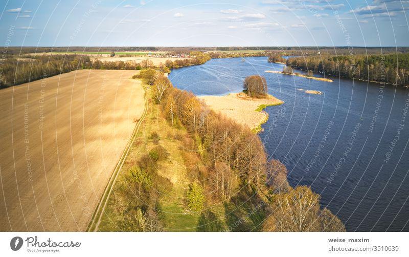 Frühlingswindiger Tag. Plätschert auf dem Wasser. Fluss mit Insel-Luftaufnahme. Wind kräuselt See Flussufer Wetter Stausee Antenne Wolken grün ländlich Pflanze