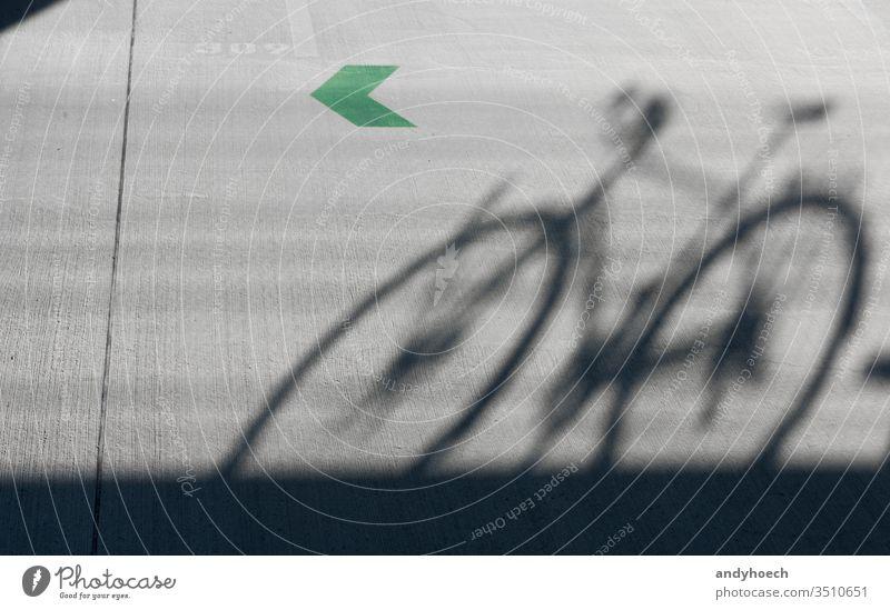 Ein Schatten eines Rennrads mit grünem Pfeil 309 abstrakt Architektur Hintergrund Fahrrad Radfahren schwarz Großstadt Farbe Mitteilung Konzept Beton