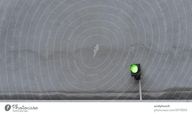 Die Ampel leuchtet grün vor der grauen Wand Unfall Architektur Autorität Hintergrund Großstadt Farbe Konzept Kontrolle Textfreiraum Gefahr Regie Laufwerk fahren