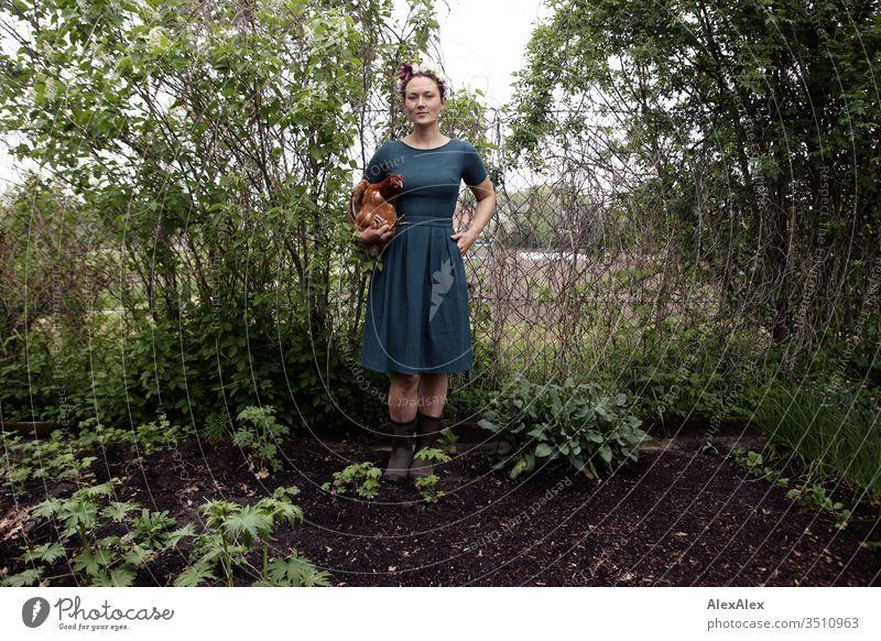 Junge Frau mit Blumenkranz im Haar steht im Garten hält braunes Huhn im Arm Zentralperspektive Schwache Tiefenschärfe Tag Außenaufnahme Farbfoto Idylle feminin