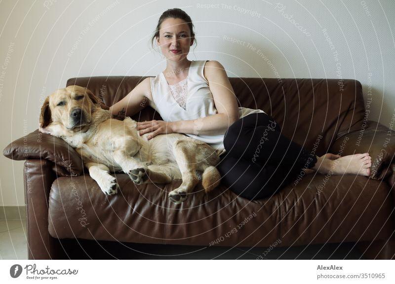 Blonder Labrador und junge Frau sitzen auf einer braunen Ledercouch Haustier Hund blond niedlich liegt sitzt Jugendliche 18-30 Jahre Couch innenaufnahme schlank