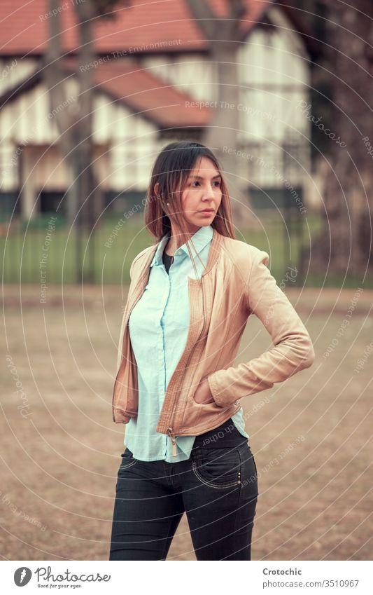 Frau steht auf der Straße mit abgewandten Händen in Lederjacke vertikal Porträt jung Mädchen feminin Haus Gebäude Park Baum Natur Herbst drehen. Verkleidung