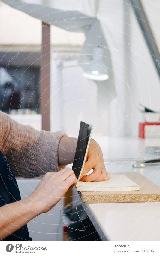 Person, die den Rücken eines Buches näht Nähen Draht Garn feststehend Hände Papier Buchbinderei drucken Bucheinband handgefertigt Gerät künstlerisch Bücher