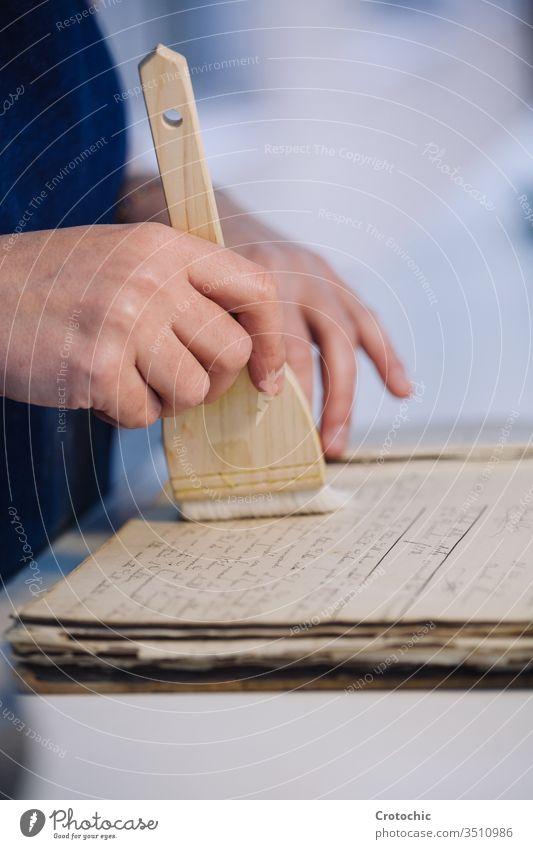 Person, die eine Seite eines alten Buches mit einer Bürste reinigt, um sie zu reparieren antik Hand Arbeiter Reparatur Sauberkeit weich Pflege vertikal