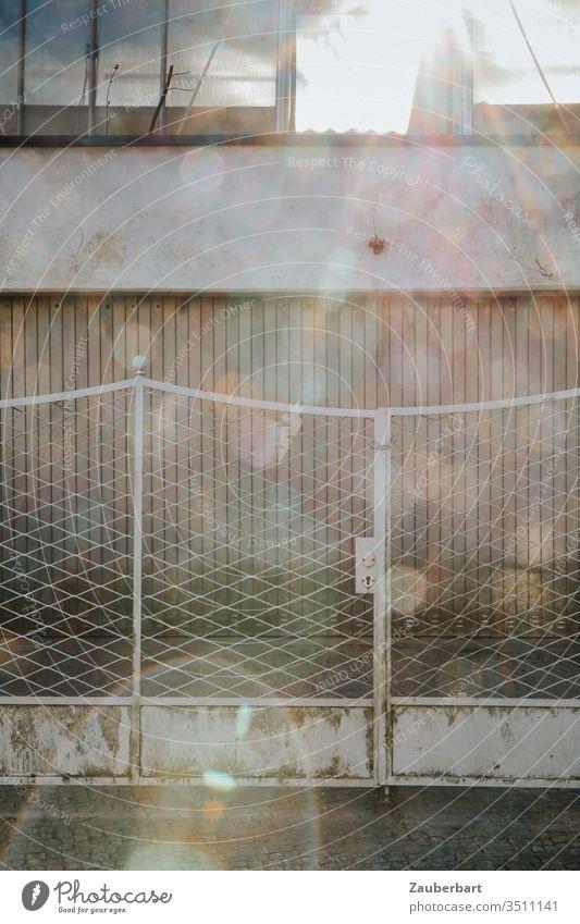 Garagentor mit Zaun in lichtem Grau mit zahlreichen Lens Flares grau trist Sonne Gegenlicht Lichtflecke Linsenreflexion Einfahrt Tor