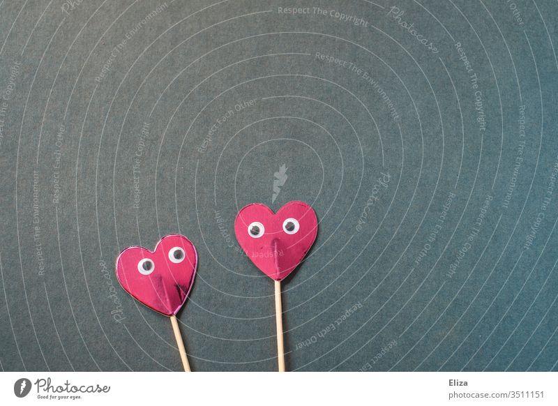 Zwei rosa Herzen am Stiel mit Augen, die sich anschauen zwei Wackelaugen verliebt liebe Gefühle betrachten blau rot Valentinstag Paar Liebespaar Romantik