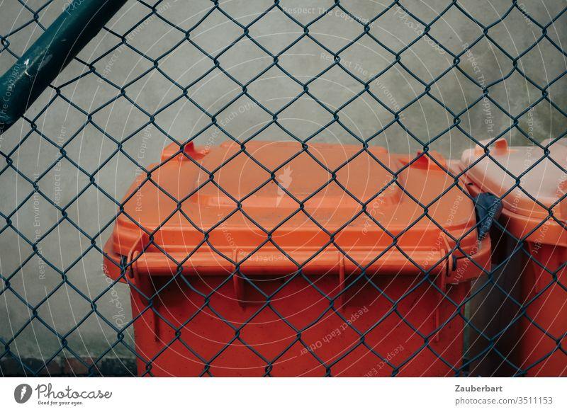 Mülltonne in orange hinter grünem Maschendrahtzaun Entsorgung Stadtreinigung Zaun Deckel Recycling Kunststoff Wand grau