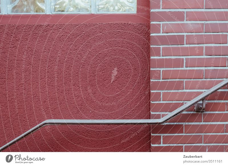 Aufsteigender Handlauf vor ziegelroter Wand Geländer Stahl Ziegel Mauer Backstein Putz Fassade Backsteinwand Strukturen & Formen Bauwerk abstrakt graphisch