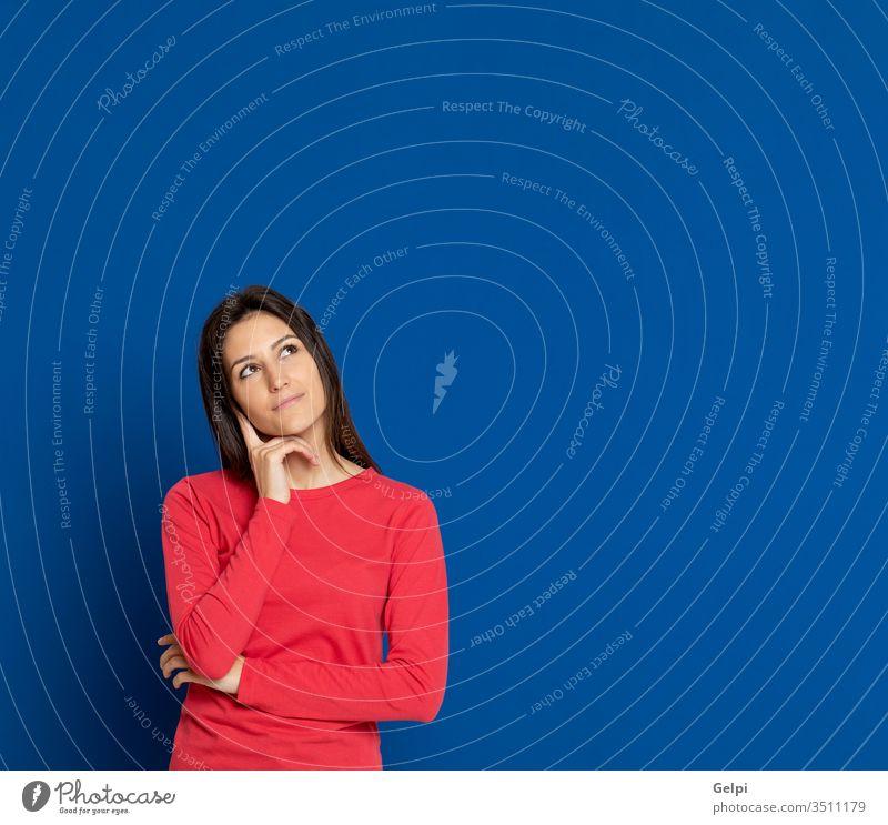 Brünette junge Frau trägt ein rotes T-Shirt Mädchen Person blau nachdenklich Geist Finger besinnlich Denken sich[Dat] einbilden Vorstellungskraft Idee
