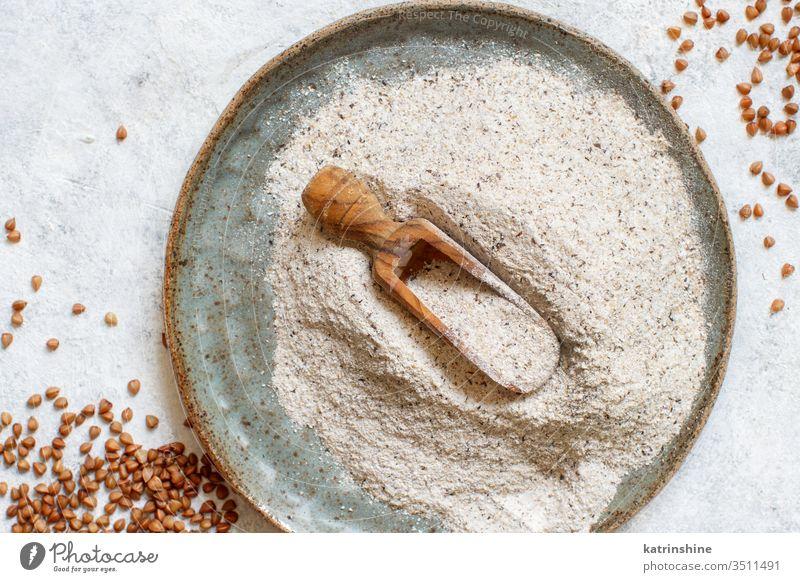 Buchweizenmehl in einem Teller mit einem Löffel und Buchweizenkorn Mehl Lebensmittel Bestandteil Korn glutenfrei Draufsicht Schalen & Schüsseln Serviette