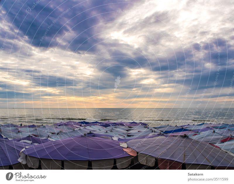 Großer Sonnenschirm entlang des Strandes überfüllt Regenschirm Himmel dunkel Cloud wolkig im Freien Sommer MEER blau Schönheit weiß Feiertag reisen Urlaub Meer