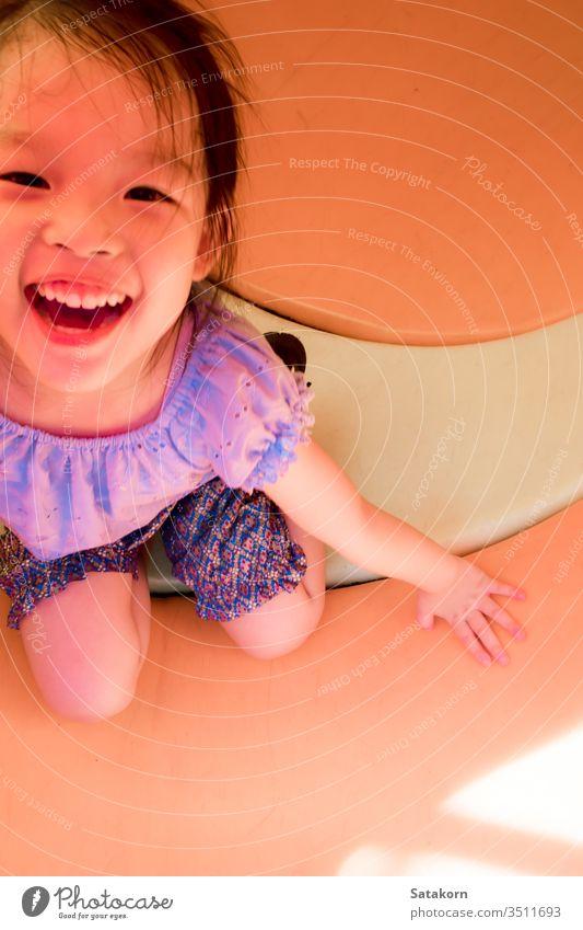 Kleines asiatisches Mädchen spielt gerne auf dem Spielplatz im Freien wenig Lächeln Kinder Glück Spaß genießen niedlich Spielen Aktivität Kindheit spielerisch
