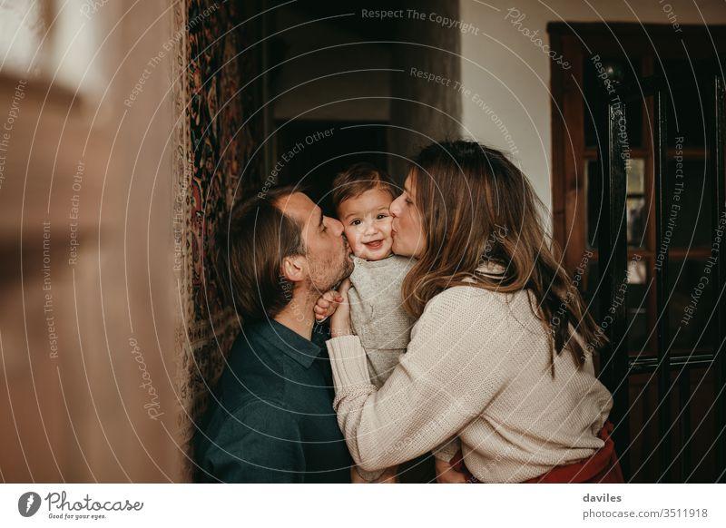 Liebliches Kleinkind, das zu Hause von Mama und Papa geküsst wird. schön gutaussehend weiß Kuss im Innenbereich Lächeln lieblich heiter positiv Menschen Raum