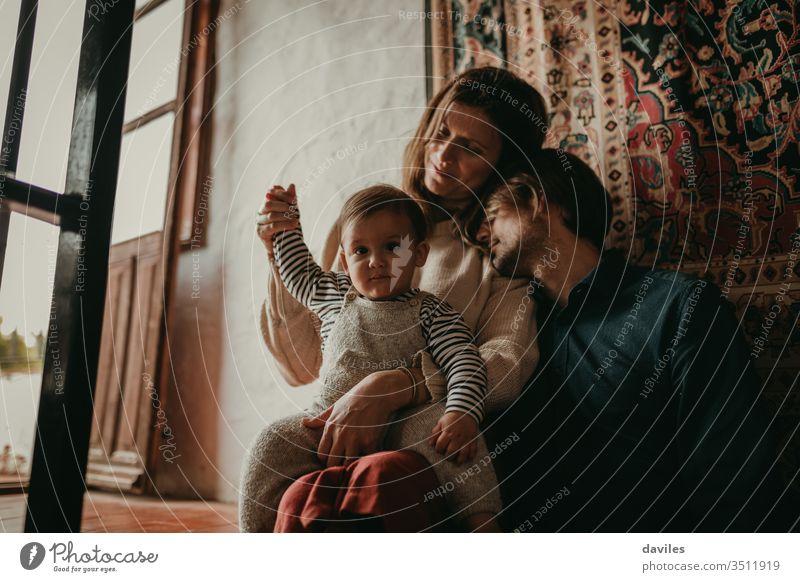 Wunderschönes Porträt eines süßen Paares, das zu Hause auf der Treppe sitzt, während es sich mit seinem Sohn ausruht. Schönes Licht, das durch das Fenster eindringt.