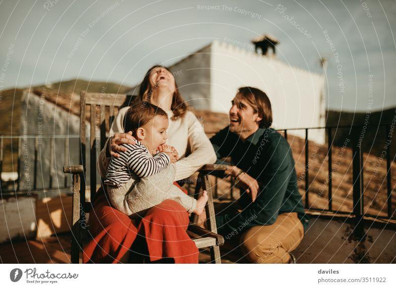 Eltern lachen und amüsieren sich mit ihrem kleinen Sohn, der auf der heimischen Terrasse bei schönem Sonnenuntergangslicht sitzt. wirklich authentisch