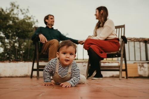 Süßer Säugling, der von seinen Eltern, die im Hintergrund sitzen, wegkrabbelt. Das Baby schaut in die Kamera. Vaterschaft niedlich Auge Haus heiter sprechend