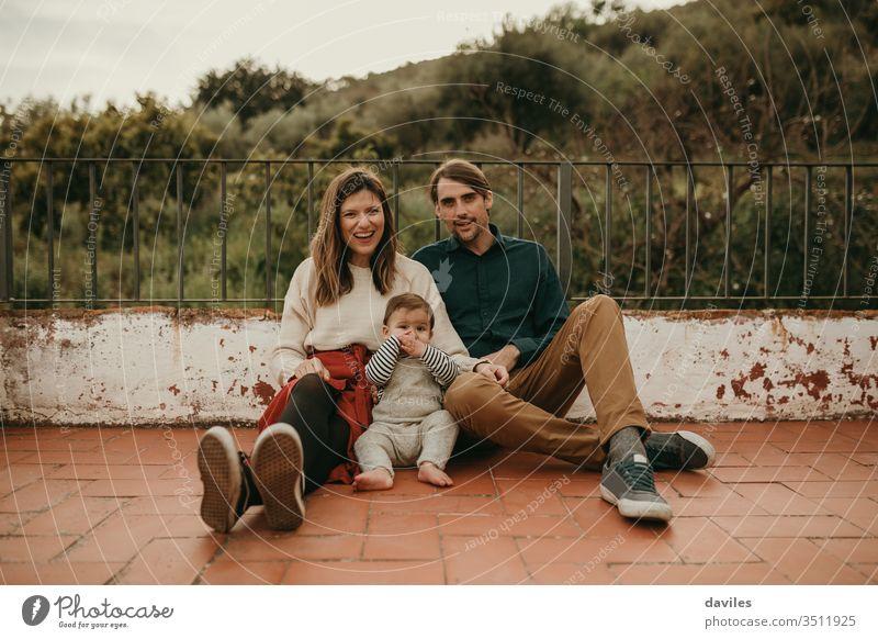 Fröhliches Familienporträt mit Mann und Frau, die mit ihrem Baby auf dem Boden auf der heimischen Terrasse sitzen. wirklich authentisch alternativ patio heiter