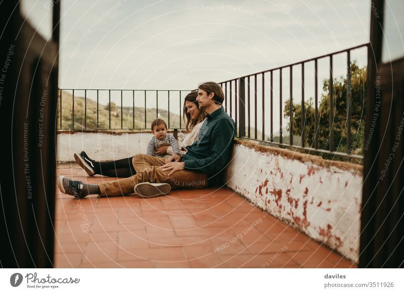 Glückliche Familie mit Mann und Frau, die mit ihrem Baby auf der heimischen Terrasse auf dem Boden sitzen, mit entspanntem Ausdruck. wirklich authentisch