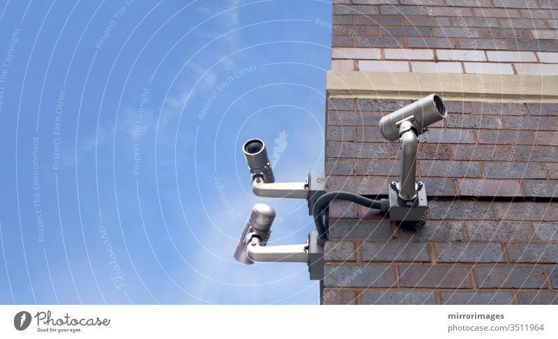 ecke eines Ziegelsteinhauses im Freien mit 3 Überwachungskameras, die an einem schönen Tag in verschiedene Richtungen zeigen Gebäude Fotokamera cctv Großstadt