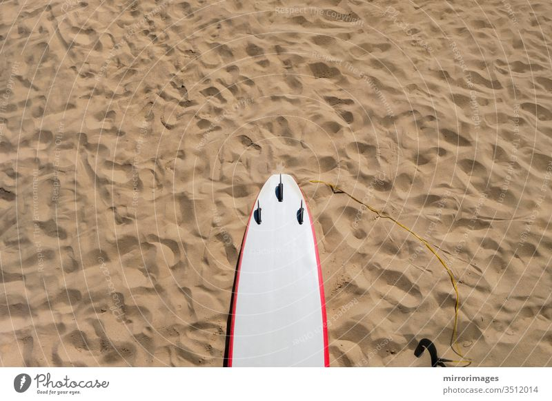 Thruster 3-Flossen-Rückseite eines Shortboard-Surfbretts mit weiß-rotem Nadelstreifen auf Sandstrand mit Fußabdrücken shortboard funboard Triebwerk drei Flosse