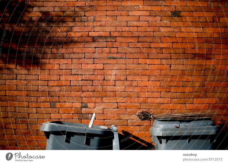 Mülleimer an die Wand schließen Baustein Backsteinwand ziegelrot Ziegelbauweise Architektur keine Menschen Müllhalde Textfreiraum Schatten Besen Besenstiel