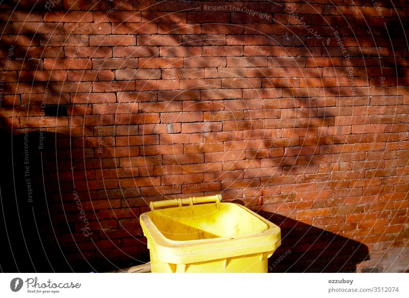 Mülleimer schließen Wand Baustein Backsteinwand Textfreiraum gelb rot Müllhalde Müllbehälter Schatten Einfachheit Schattenspiel Pflanze Umwelt Umweltschutz