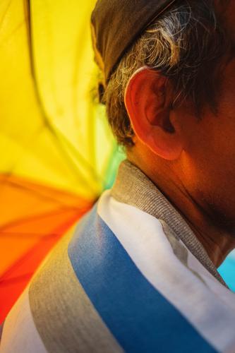 Nahaufnahme des Ohrs eines alten Mannes mit einem Regenbogenschirm im Vordergrund alter Mann Holunderbusch regenbogenfarben Regenbogentuch Farbe Farben