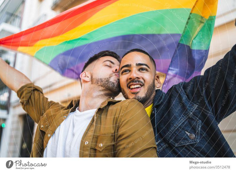 Schwules Paar umarmt und zeigt seine Liebe mit der Regenbogenfahne. lgbt Fahne Homosexualität Freiheit schwul zwei Partner stolz Nähe außerhalb Vielfalt