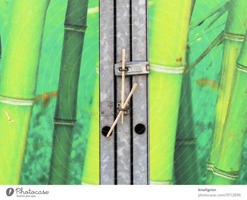Müllcontainer mit Bambus-Dekorfolie beklebt, verschlossen mit zwei Holzstäbchen Verschluss grün Asien Bambusrohr Japan Pflanze Außenaufnahme Farbfoto Metall