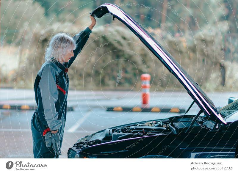 Attraktive junge blonde Frau, die eine Automechaniker-Uniform trägt und das Auto repariert Automobil PKW Kaukasier Reparatur Fahrzeug attraktiv Hintergrund