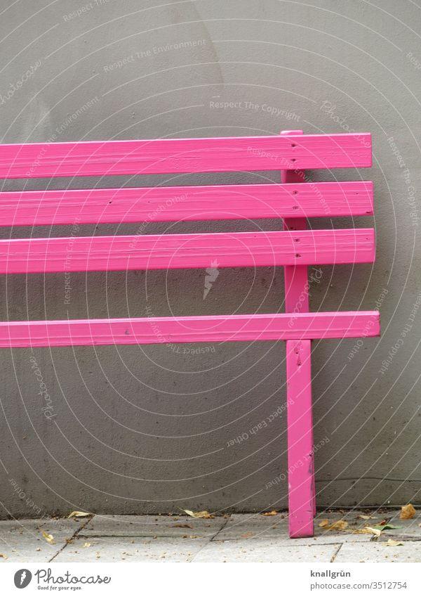 Pinkfarbene Holzbank vor grauer Hauswand Sitzgelegenheit Möbel Bank Erholung Pause Außenaufnahme Menschenleer Farbfoto Tag ruhig Textfreiraum oben
