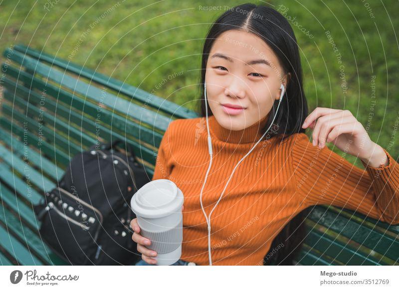 Asiatische Frau, die Musik hört. Kaffee Mädchen asiatisch Park im Freien jung schön Kopfhörer zuhören Person außerhalb Lifestyle Chinesisch Großstadt grün