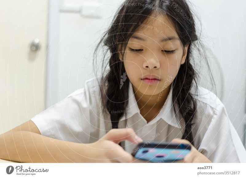 Kinder, die nach Smartphone-Spielen süchtig sind Sucht Asien asiatisch schön Zelle Funktelefon Kindheit Mitteilung Konzept niedlich digital Bildung genießen