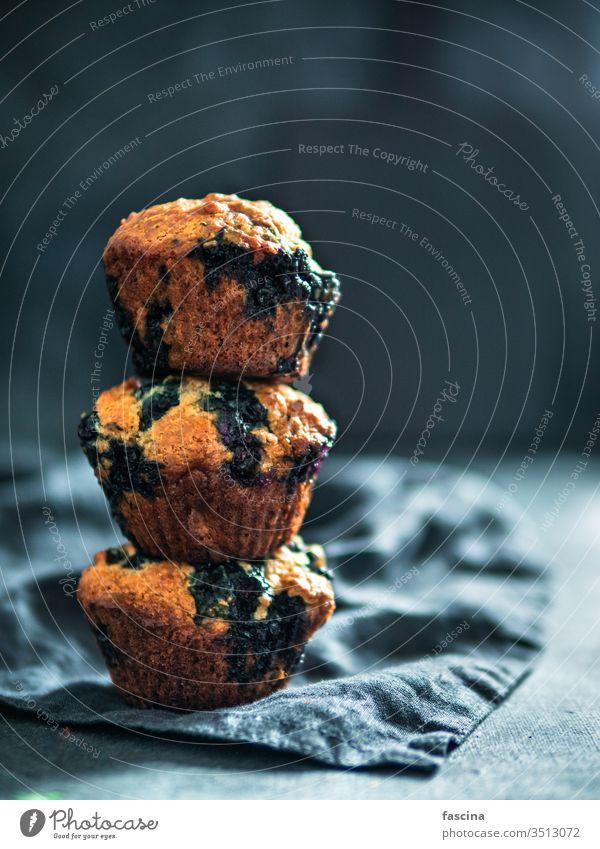 Hausgemachte Blaubeer-Muffins auf dunklem Hintergrund. kalorienarm selbstgemacht Blaubeeren drei Stapel niemand Draufsicht oben vertikal Lebensmittel Dessert